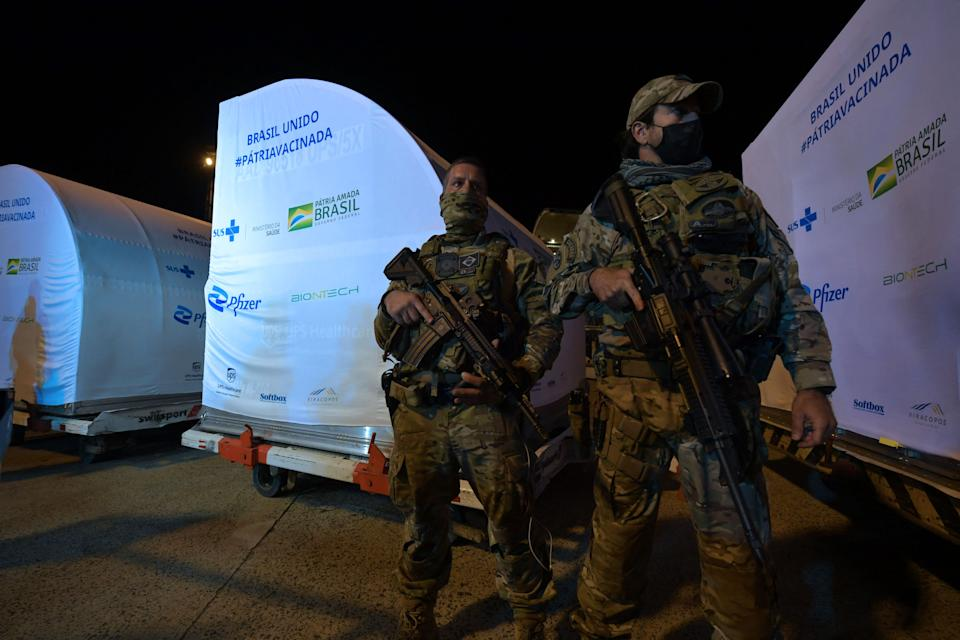 Soldiers guard a container with 1,000,000 doses of the Pfizer-BioNTech vaccine against COVID-19 upon its arrival at the Viracopos International Airport in Campinas, some 100 km from Sao Paulo, Brazil on April 29, 2021. - Brazil received Thursday a first lot of 1,000,000 doses of the Pfizer-BioNTech vaccine developed by US drugmaker Pfizer and BioNTech of Germany. (Photo by NELSON ALMEIDA / AFP) (Photo by NELSON ALMEIDA/AFP via Getty Images)