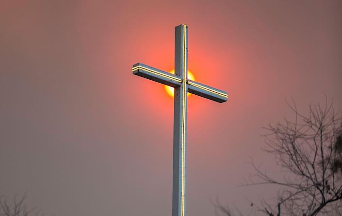 Smoke from a wildfire in California appears behind a church cross. (Photo: Daniel Knighton via Getty Images)