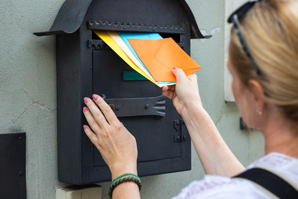 Woman is holding colorful envelopes. Postal worker delivering correspondence