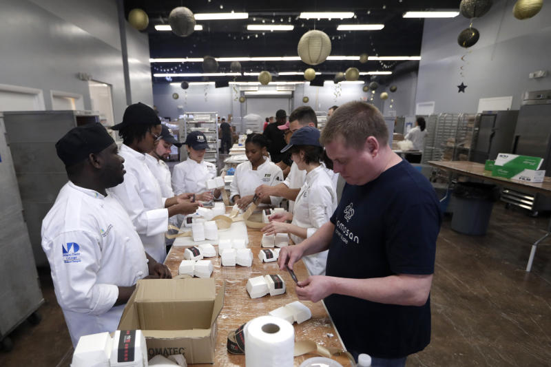 In this Thursday, Feb. 20, 2020 photo. students with Florida International University's culinary school prepare packaging for the Morimoto entry in the burger bash competition at the Miami Rescue Mission in Miami. From Rachael Ray to Bobby Flay, the biggest names in the culinary world are in Miami starting Thursday for the South Beach Wine and Food Festival. And they're getting help in their prep kitchen from an unlikely source, a local homeless shelter. The festival partnered with the Miami Rescue Mission and Florida International University's culinary school. (AP Photo/Lynne Sladky)