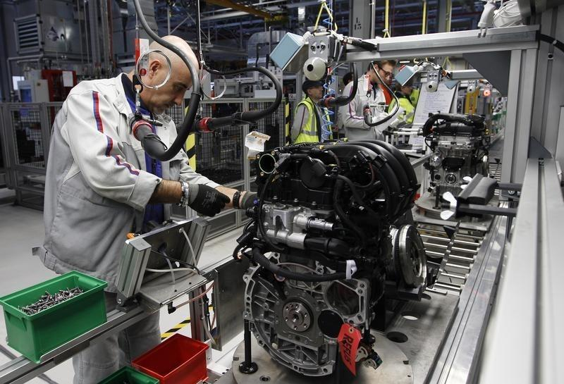 """Employees of French carmaker PSA Peugeot Citroen work on the new engine """"EB"""" assembly line at the company engines factory in Tremery near Metz"""