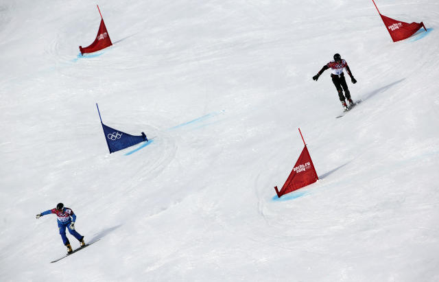 Ukraine's Yosyf Penyak, left, competes against Bulgaria's Radoslav Yankov during men's snowboard parallel giant slalom qualifying at the Rosa Khutor Extreme Park, at the 2014 Winter Olympics, Wednesday, Feb. 19, 2014, in Krasnaya Polyana, Russia. (AP Photo/Andy Wong)