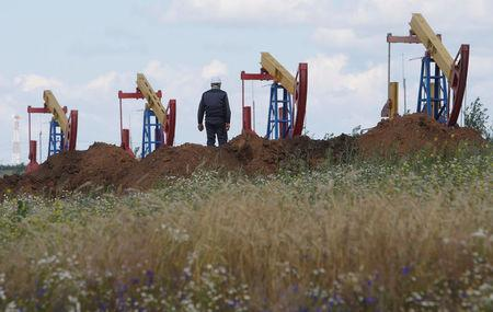 FILE PHOTO: A worker stands in front of pump jacks at the Ashalchinskoye oil field owned by Russia's oil producer Tatneft near Almetyevsk