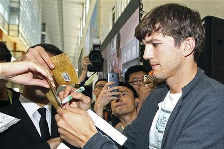 """U.S. actor Ashton Kutcher signs autographs for his fans during a promotional tour for the movie """"Jobs"""" in Beijing August 25, 2013. REUTERS/Stringer/Files"""