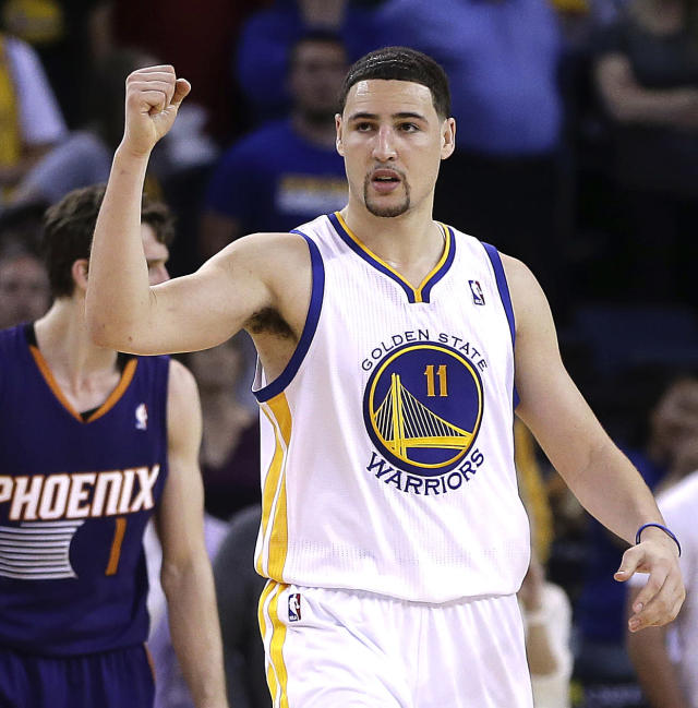 Golden State Warriors' Klay Thompson (11) celebrates a score against the Phoenix Suns during the second half of an NBA basketball game Sunday, March 9, 2014, in Oakland, Calif. (AP Photo/Ben Margot)