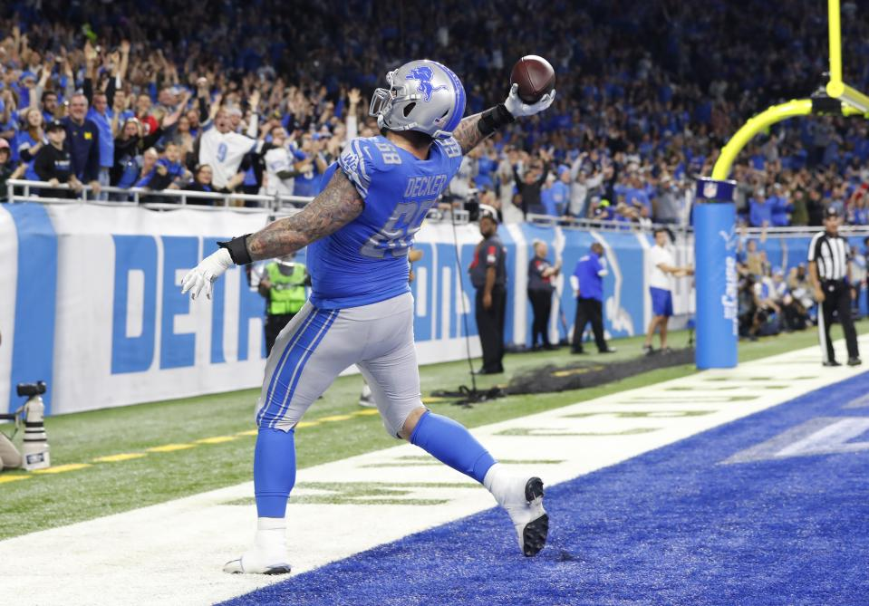 Detroit Lions offensive tackle Taylor Decker throws the ball to the fans after running 11-yards for a touchdown in a 2018 game. (AP Photo/Paul Sancya)
