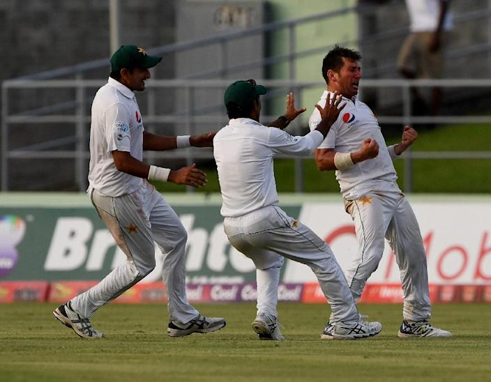 Yasir Shah (R) celebrates taking the final wicket as Pakistan beat the West Indies for a 2-1 series win at the Windsor Park Stadium in Roseau, Dominica (AFP Photo/MARK RALSTON)