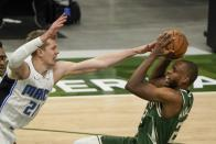 Milwaukee Bucks' Khris Middleton shoots over Orlando Magic's Moritz Wagner during the first half of an NBA basketball game Tuesday, May 11, 2021, in Milwaukee. (AP Photo/Morry Gash)