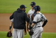 New York Yankees pitching coach Matt Blake, left, talks with, starting pitcher Jameson Taillon, center, and catcher Gary Sanchez, right, during a mound visit in the third inning of a baseball game against the Texas Rangers in Arlington, Texas, Tuesday, May 18, 2021. (AP Photo/Tony Gutierrez)