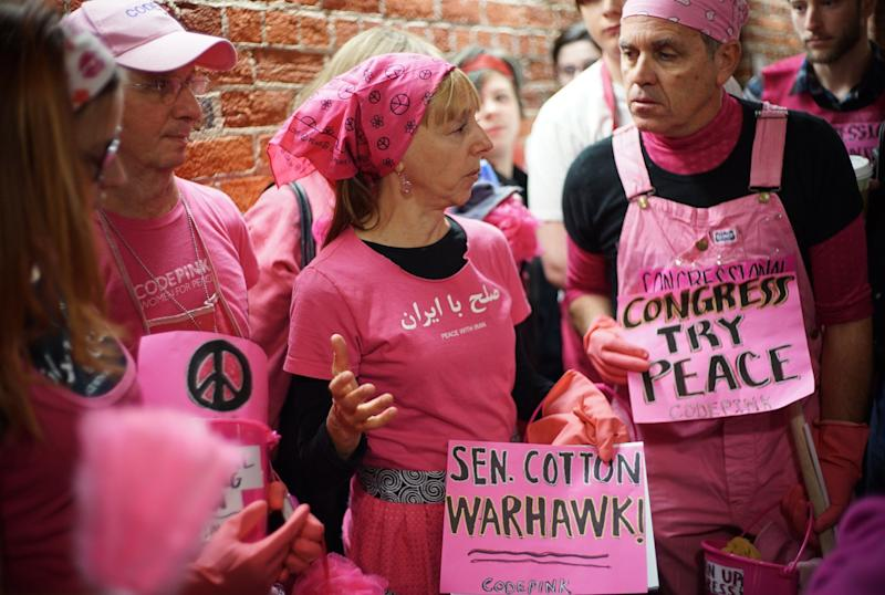 "Code Pink peace activists discuss a letter to Iran's leaders written by Sen. Tom Cotton (R-Ark.) outside his office in the Russell Senate Office Building on Capitol Hill on March 19, 2015. The group organized a ""spring cleaning of Congress."""