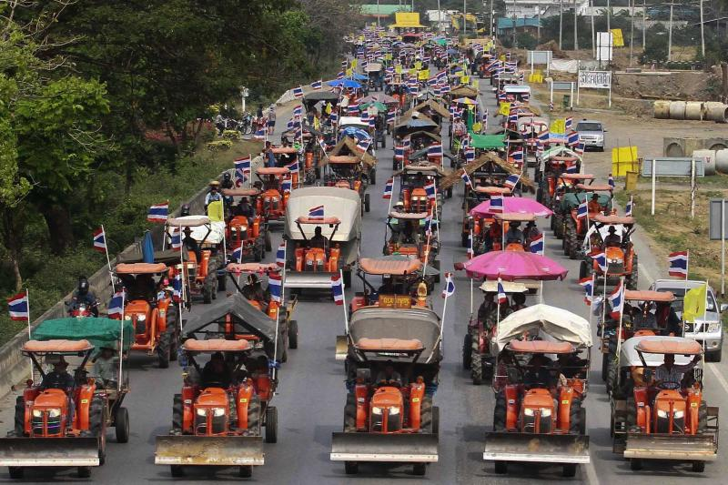 """Farmers drive their tractors and other farming vehicles on a road in Ang Thong province, towards Bangkok, February 20, 2014. More than 1,000 farmers, many riding in farm trucks, are travelling in a convoy towards Bangkok from the rice-growing central plains and were due to reach the city overnight or on Friday. Chada Thaiseth, a former member of parliament, said he would lead farmers on Friday to Bangkok's Suvarnabhumi Airport, blockaded for eight days by royalist, anti-Thaksin """"yellow shirts"""" in 2008. REUTERS/Stringer (THAILAND - Tags: POLITICS CIVIL UNREST AGRICULTURE) ATTENTION EDITORS - NO SALES. NO ARCHIVES. FOR EDITORIAL USE ONLY. NOT FOR SALE FOR MARKETING OR ADVERTISING CAMPAIGNS. THAILAND OUT. NO COMMERCIAL OR EDITORIAL SALES IN THAILAND"""