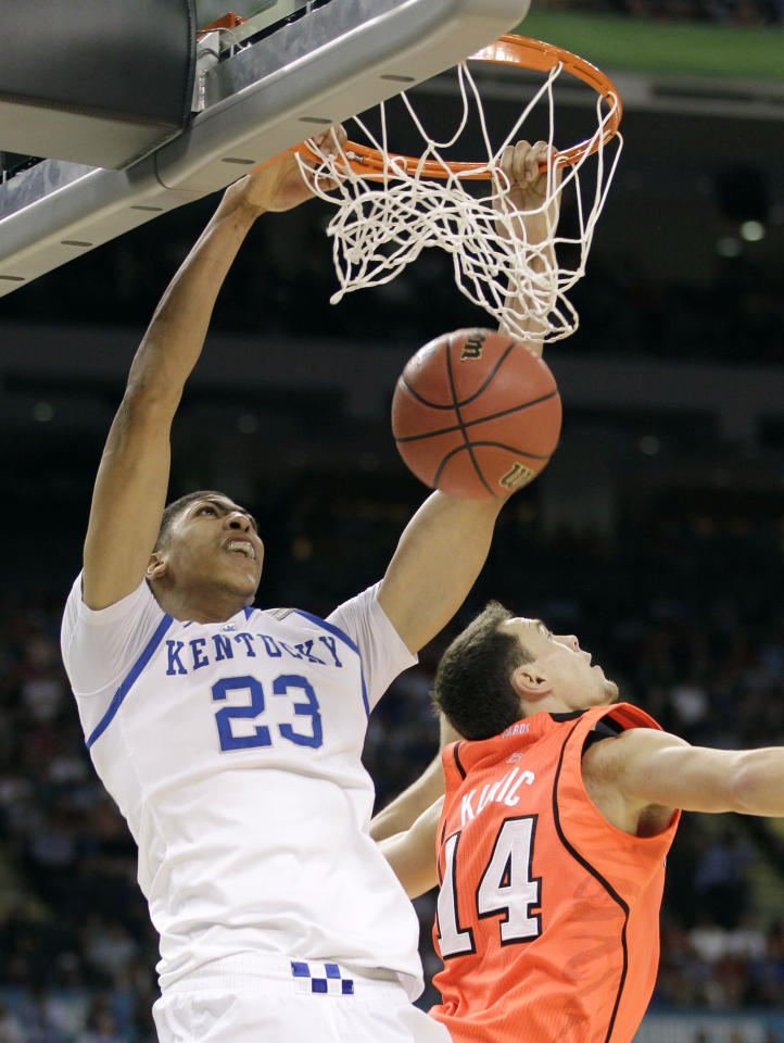 Kentucky's Anthony Davis (23) dunks the ball over Louisville's Kyle Kuric during the first half of an NCAA Final Four semifinal college basketball tournament game Saturday, March 31, 2012, in New Orleans. (AP Photo/Mark Humphrey)