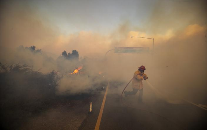 Firefighter Vince Valdivia, standing on a roadway as he sprays a hose, is surrounded by heavy smoke.