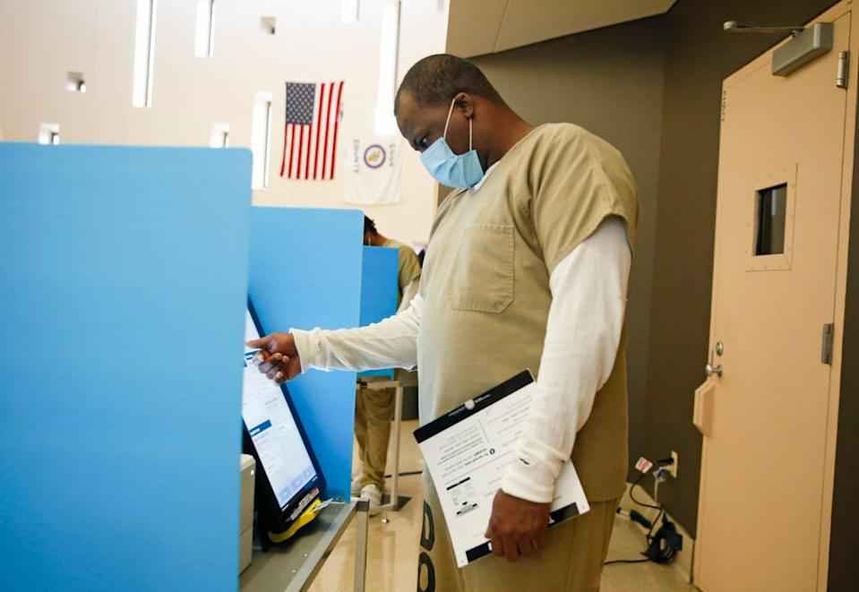 A Cook County jail detainee uses a touch screen to cast his votes at a polling in the facility set up for early voting on October 17, 2020 in Chicago, Illinois. It is the first time pretrial detainees in the jail will get the opportunity for early voting in a general election.