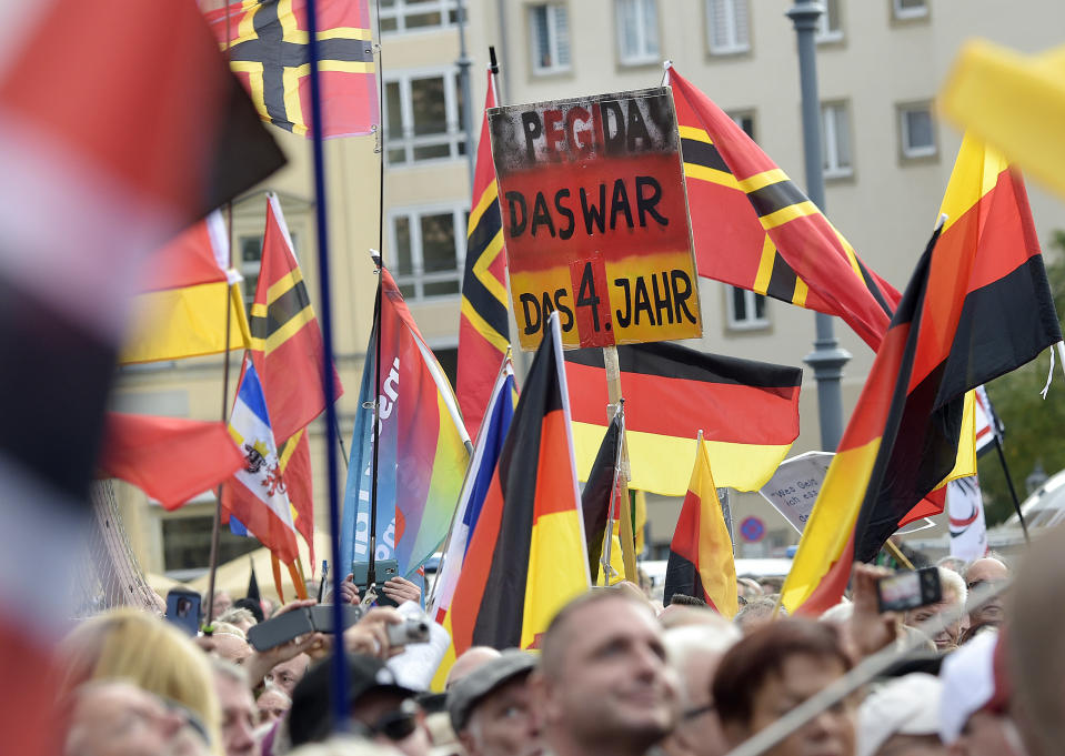 """People carry a sign reading """"PEGIDA that was your fourth year"""" during a rally of PEGIDA (Patriotic Europeans against the Islamization of the West) in Dresden, Germany, Sunday, Oct.21, 2018. (AP Photo/Jens Meyer)"""