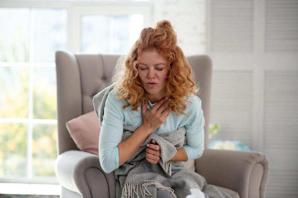Curly woman feeling bad and suffering from strong cough while having flu