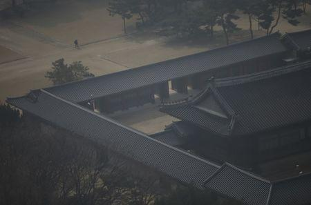 FILE PHOTO: People take a walk during a lunch break on a hazy day at Deoksu Palace in Seoul