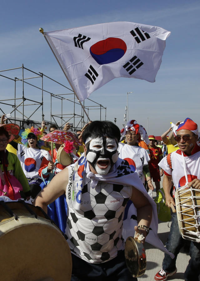 South Korean fans cheer their team's victory before the group H World Cup soccer match between South Korea and Belgium outside of the Itaquerao Stadium in Sao Paulo, Brazil, Thursday, June 26, 2014. (AP Photo/Lee Jin-man)