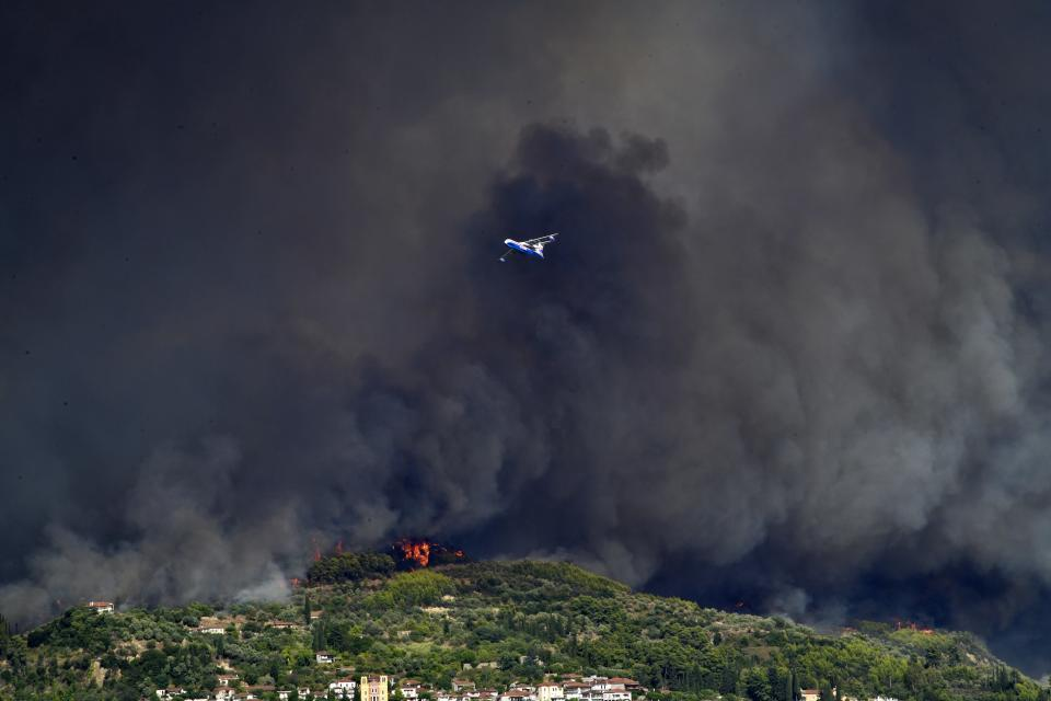 A Russian aircraft operates during a wildfire near ancient Olympia, Wednesday, Aug. 4, 2021. Greece evacuated people in boats from an island beach Wednesday amid heavy smoke from a nearby wildfire and fire crews fought elsewhere to keep flames away from the birthplace of the ancient Olympic Games as the country sweltered under a record heat wave. (Giannis Spyrounis/ilialive.gr via AP)
