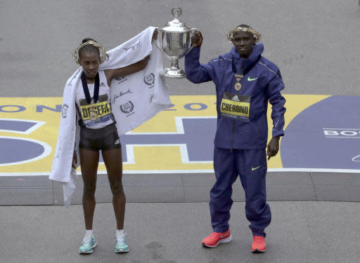 Worknesh Degefa, left, of Ethiopia, winner of the women's division, and Lawrence Cherono, right, of Kenya, winner of the men's division of the 123rd Boston Marathon, hold the trophy at the finish line on Monday, April 15, 2019, in Boston. (AP Photo/Charles Krupa)