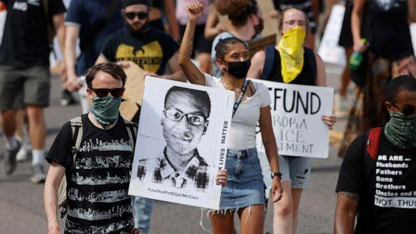 PHOTO: Demonstrators march with placards during a rally in response to the death of Elijah McClain in Aurora, Colo., June, 27, 2020. (David Zalubowski/AP, FILE)