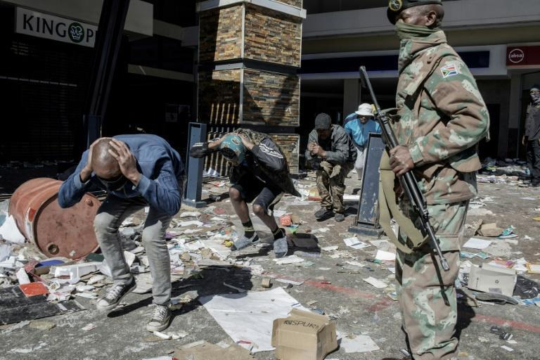 Police and troops detaining suspected looters at the Jabulani shopping mall in Soweto on Tuesday