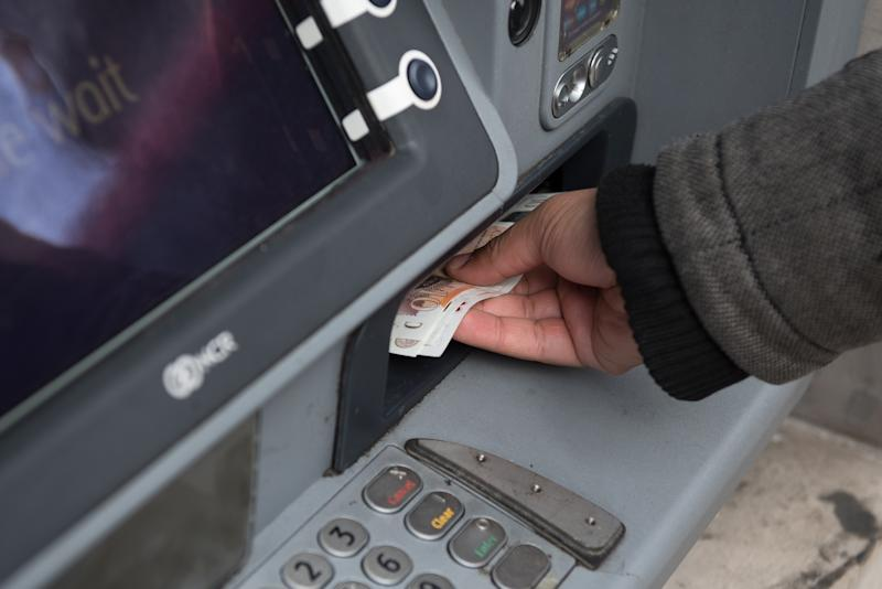 LONDON, ENGLAND - MARCH 10: A member of the public withdraws cash from a cash machine on March 10, 2020 in London, England. It has been reported that a person could also contract the new (Covid-19) coronavirus by touching surfaces or objects that have viral particles on them and then touching their mouth, nose, or eyes. The lifespan of the virus on a surface can depend the surrounding temperature, humidity, and type of surface ranging from hours or days. Today the number of coronavirus cases in the UK has risen to 373 a rise of 54 since yesterday. (Photo by John Keeble/Getty Images)