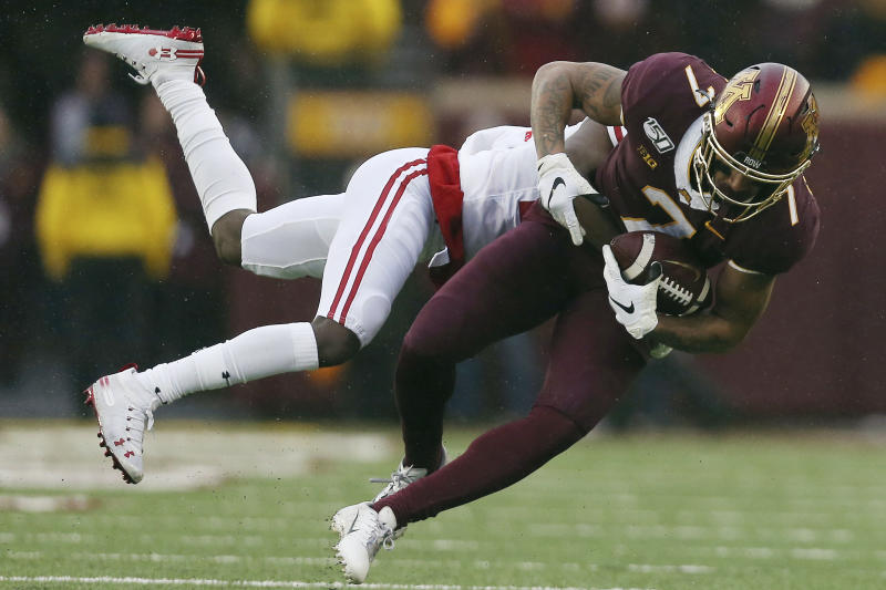 Minnesota wide receiver Chris Autman-Bell (7) is tackled by Wisconsin cornerback Semar Melvin (20) during an NCAA college football game, Saturday, Nov. 30, 2019, in Minneapolis. (AP Photo/Stacy Bengs)