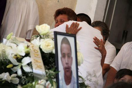 FILE PHOTO: Relatives cry beside a coffin containing Rodriguez during his funeral in Nogales
