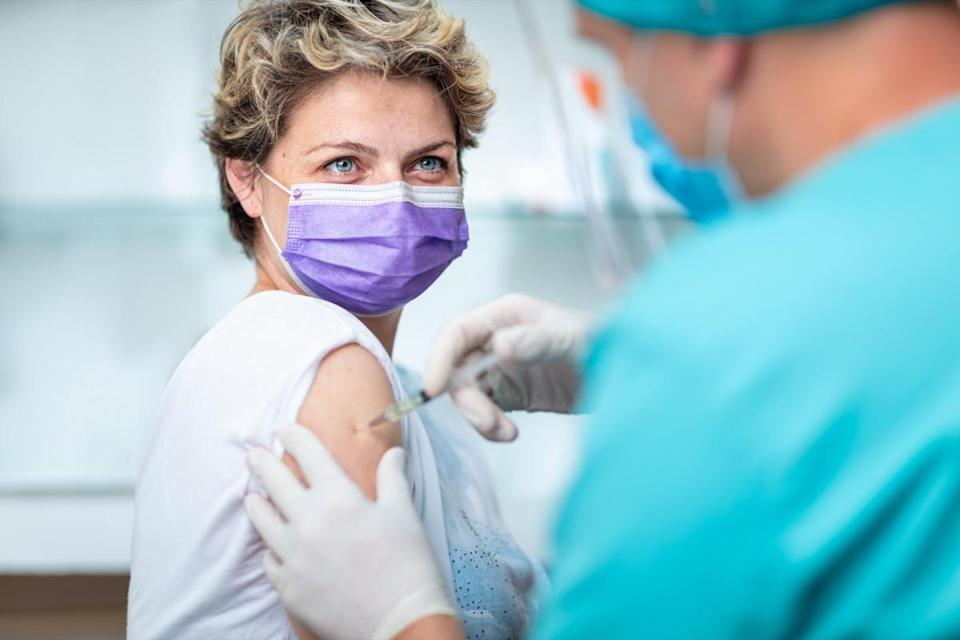 Female patient smiling behind the face mask and with her eyes, while getting flu shot
