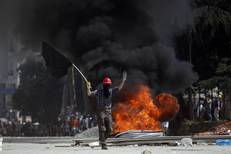 <p> A protester gestures to riot policemen as he walks in front of a burning barricade during clashes in Taksim square in Istanbul, Tuesday, June 11, 2013. Hundreds of police in riot gear forced through barricades in Istanbul's central Taksim Square early Tuesday, pushing many of the protesters who had occupied the square for more than a week into a nearby park. (AP Photo/Kostas Tsironis)</p>