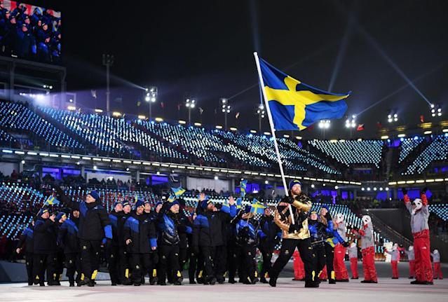 <p>Flag bearer of Sweden Niklas Edin and teammates enter the stadium wearing chic knit hats and pants with a minimalistic yellow block motif to symbolize their flag, accompanied by navy-and-black puffer jackets. Leave it to the Swedes to stay stylish no matter the event. (Photo: Matthias Hangst/Getty Images) </p>
