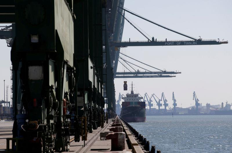FILE PHOTO: A container is carried away from a cargo ship at Tianjin Port