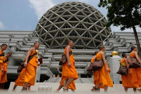 Buddhist Monks from Dhammakaya temple walk past a building inside Dhammakaya temple in Pathum Thani province