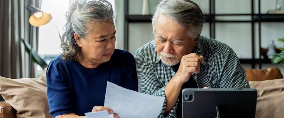 senior couple checking bills together on sofa, looking concerned.