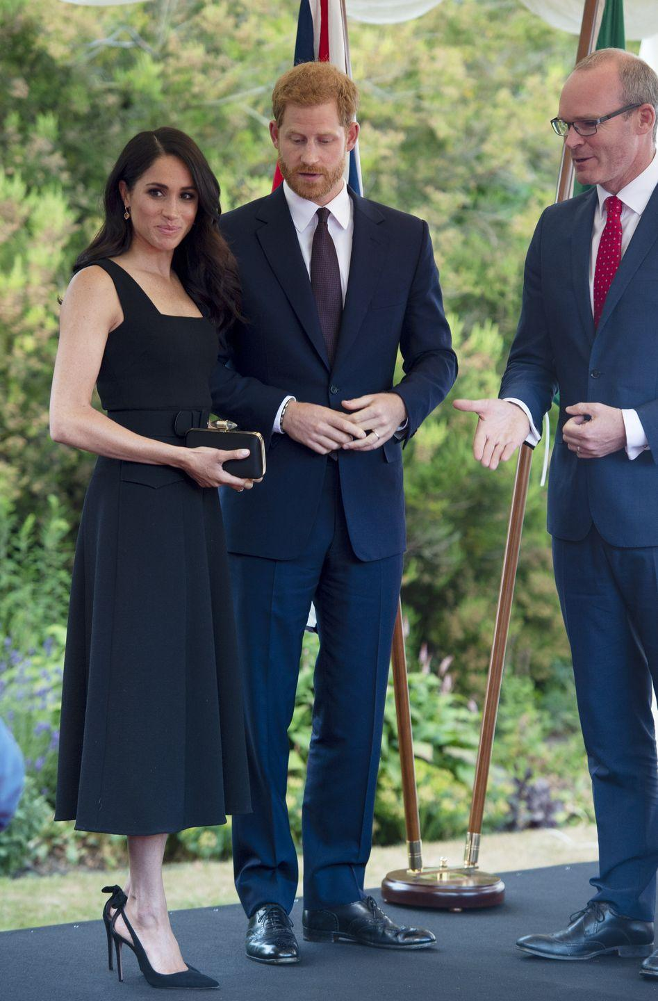 <p>For a garden party at the British Ambassador's residence in Dublin, Ireland, the Duchess of Sussex wore a black dress by Emilia Wickstead with an A-line silhouette, square neckline, and belt, July 2018.</p>