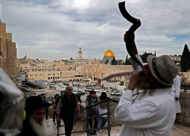 <p>A general view shows a Jewish man blowing a Shofar near the Western Wall (R) and the Dome of the Rock (C) in the Al-Aqsa mosque compound in the Old City of Jerusalem on Dec. 5, 2017. (Photo: Thomas Coex/AFP/Getty Images) </p>