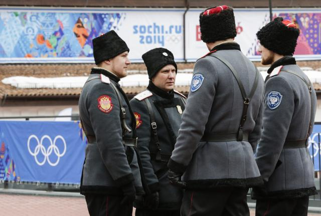 FILE - In this Jan. 30, 2014 file photo, Russian Cossack soldiers stand guard on a bridge at the ski resort Rosa Khutor in Krasnaya Polyana outside the Black Sea resort of Sochi, Russia, where the snow and sliding sports venues for the 2014 Winter Olympics are located. Around 200 Cossacks will be drafted in to provide security at 2018 World Cup games in Russia to help security forces around the stadium and airport. Some will double as entertainers with displays of horseback stunt-riding. (AP Photo/Gero Breloer, File)