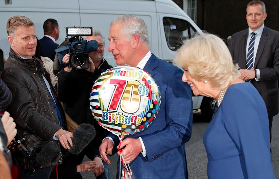 LONDON, UNITED KINGDOM - NOVEMBER 14: (EMBARGOED FOR PUBLICATION IN UK NEWSPAPERS UNTIL 24 HOURS AFTER CREATE DATE AND TIME) Camilla, Duchess of Cornwall looks on as Prince Charles, Prince of Wales receives a birthday present and helium balloon as they attends an Age UK Tea, celebrating 70 inspirational people marking their 70th birthday this year at Spencer House on November 14, 2018 in London, England. The Prince of Wales celebrates his 70th birthday today, he was born on November 14 1948 at Buckingham Palace. (Photo by Max Mumby/Indigo/Getty Images)