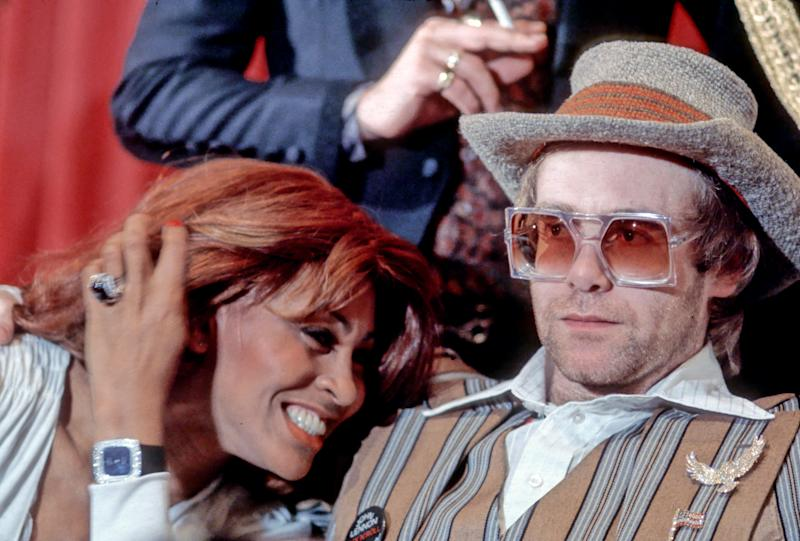 "MARCH 18: Rock and roll singer Tina Turner snuggles up to fellow performer Elton John during a press conference for the release of the rock group ""The Who's"" rock opera film ""Tommy"" in which they appear on March 18, 1975. (Photo by Michael Ochs Archives/Getty Images)"