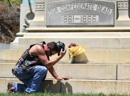 Darrin Powell, of Bullett County, Kentucky, kneels in front of a Civil War Confederate Soldier Memorial in Brandenburg, Kentucky, U.S. May 29, 2017. The Memorial was recently removed from the campus of the University of Louisville. REUTERS/Bryan Woolston