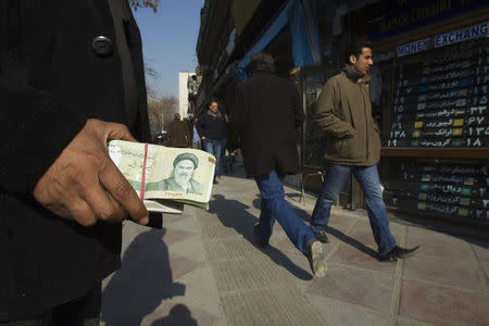 A money changer holds Iranian currency as he waits for customers in Tehran's business district