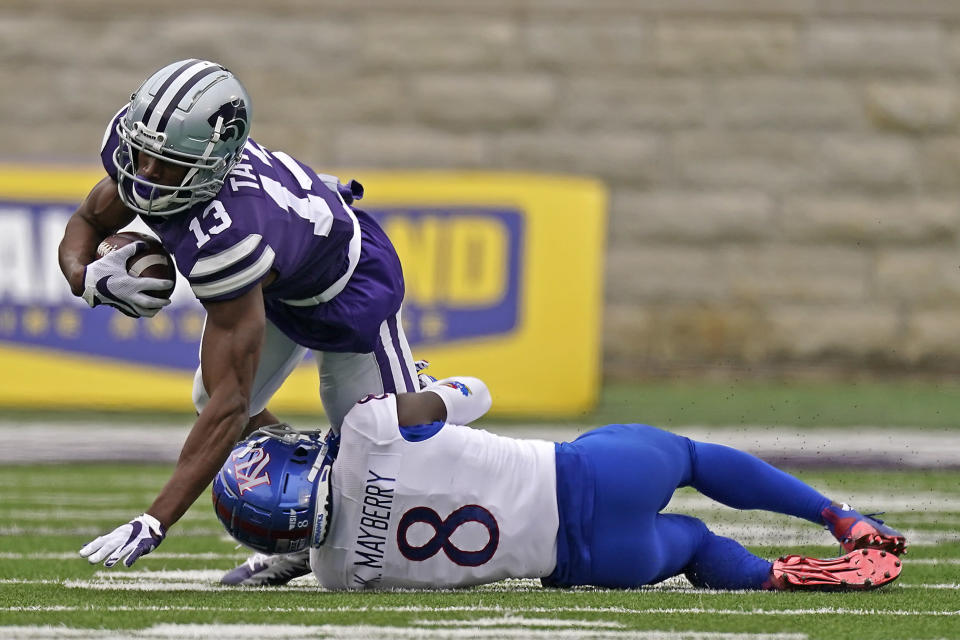 Kansas State wide receiver Chabastin Taylor (13) is tackled by Kansas cornerback Kyle Mayberry (8) during the second half of an NCAA college football game Saturday, Oct. 24, 2020, in Manhattan, Kan. Kansas State won 55-14. (AP Photo/Charlie Riedel)