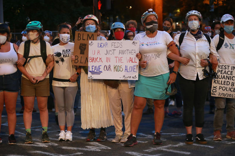 A group of mothers stand arm-in-arm outside the federal building and Justice Center in downtown Portland, Ore., on Saturday, July 18, 2020, during another night of protests in Portland. (Mark Graves/The Oregonian via AP)