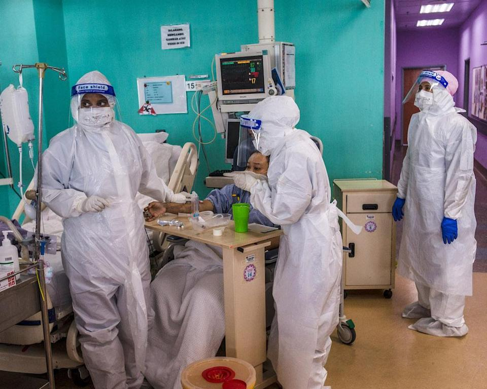 Health workers wearing PPE perform routine procedures on Covid-19 patients who have recovered and are not intubated in the ICU at Serdang Hospital. — Picture by Shafwan Zaidon