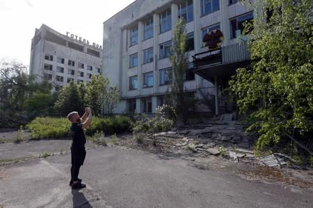 A visitor takes photos of a building in the abandoned city of Pripyat, near the Chernobyl nuclear power plant