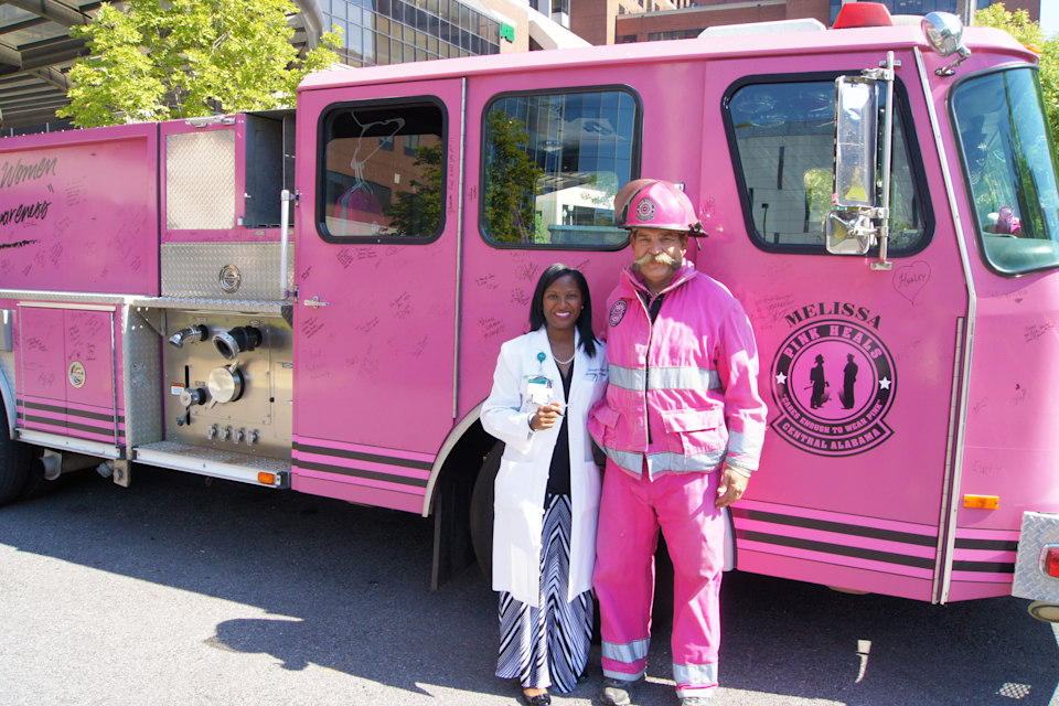 "Dr. Erica Stringer-Reasor stands next to a firefighter in front of a pink fire truck with a ""pink heals"" emblem painted on the door.."
