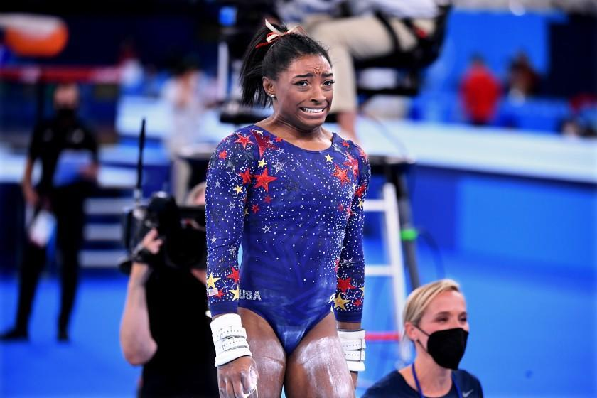 Simone Biles reacts after competing on the uneven bars at the Olympics.