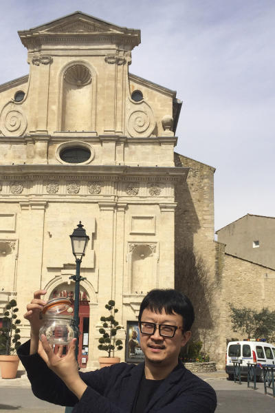 In this photo taken on March 29, 2014, Beijing artist Liang Kegang collects fresh air in the commune of Forcalquier in Provence, France. The jar of air is a piece of conceptual art to protest his home city's choking pollution. It has fetched $860 in a small auction. (AP Photo/Liang Kegang)