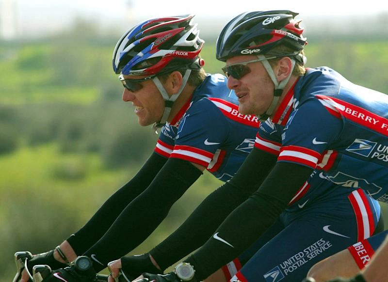 FILE - In this Feb. 19, 2004 file photo, Lance Armstrong, left, and Floyd Landis, both members of the U.S. Postal Service cycling team, smile while riding side-by-side during the second stage of the 5-day Tour of the Algarve cycling race in Algarve, southern Portugal. Attorneys for the federal government and Floyd Landis urged a judge not to dismiss the whistleblower lawsuit against Lance Armstrong, arguing the Texan and former team officials should have to pay back at least $40 million they were paid in a sponsorship deal with the U.S. Postal Service. (AP Photo/Miguel Riopa, Pool, File)